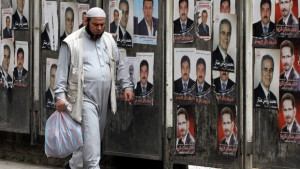 A Syrian man walks past campaign posters for the upcoming parliamentary election in Damascus, May 1, 2012. / Getty
